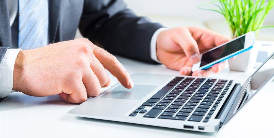 Bilde av mann med mobiltelefon og laptop.