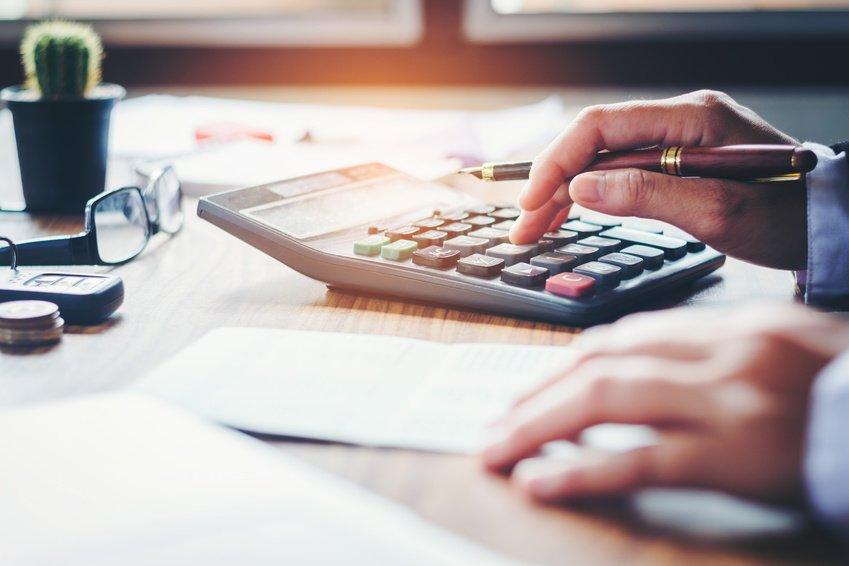 person kalkulerer kostnad ved bruk av finansagent
